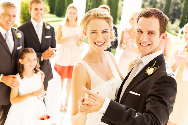 Portrait of happy couple dancing with wedding guests applauding in background during reception. Horizontal shot.
