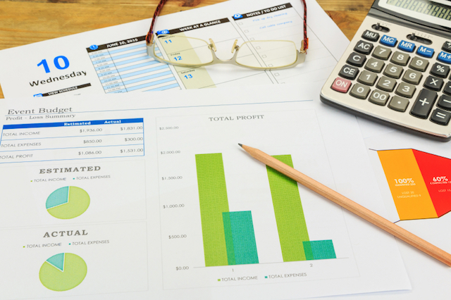 Business concept of a pencil, charts, eyeglasses, calculator