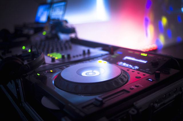DJ Console Playing Music for a Party at a Nightclub with Colored Disco Lights