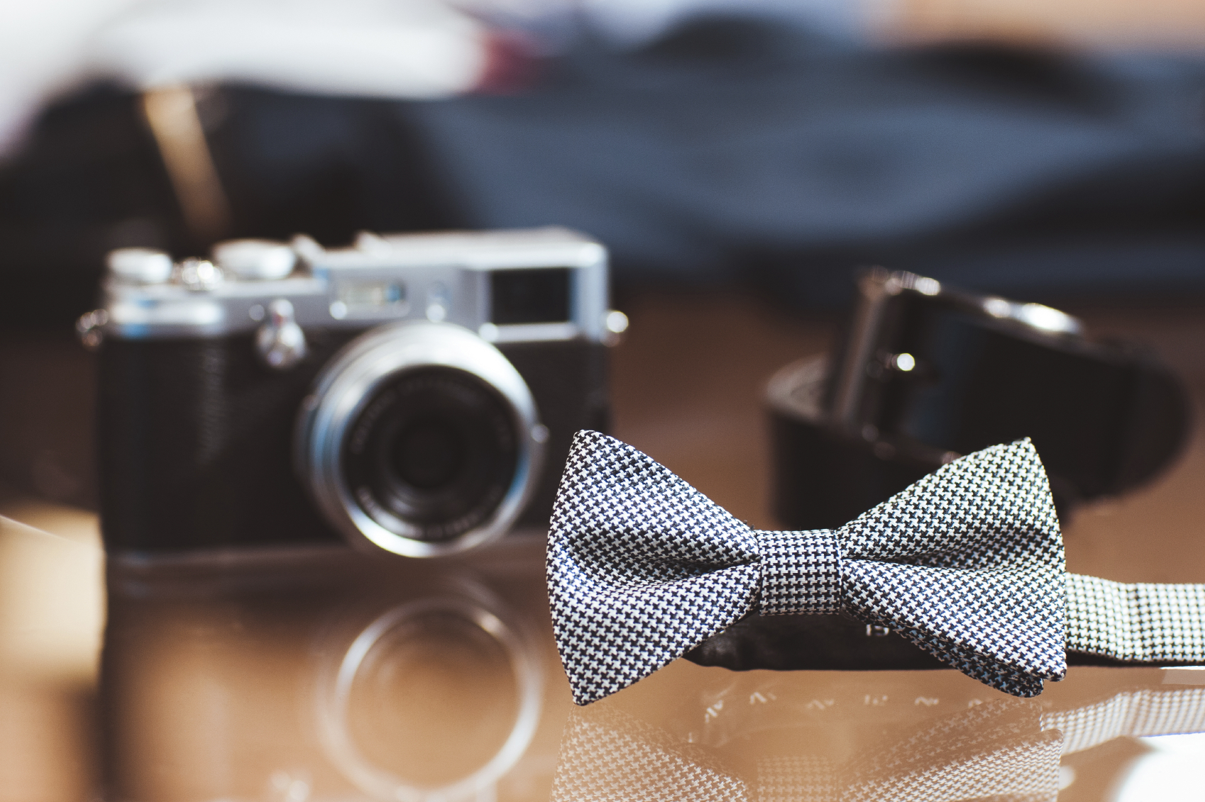 Stylish white men's bow tie, the digital camera and belt on a glass show-window of shop. set of man's casual accessories